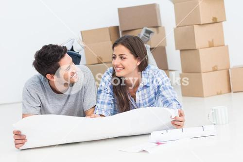 Couple lying on the floor and holding house plans