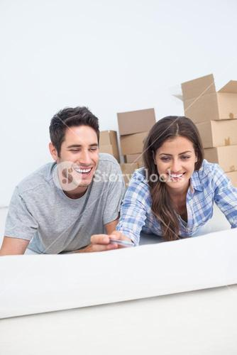 Happy couple lying on the floor and holding a house plan