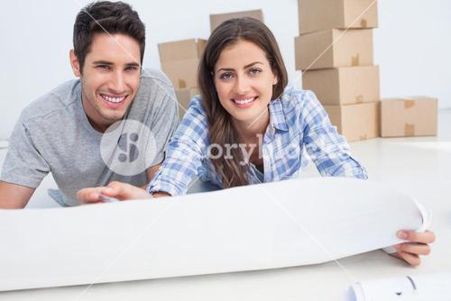 Portrait of a couple lying on the floor and holding a house plan