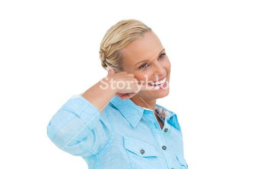 Attractive blonde doing a symbol of phone with her hand and looking something