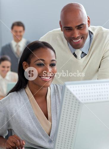 Confident businessman helping his colleague at a computer