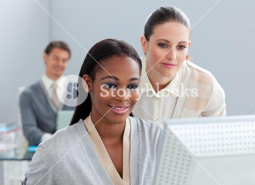 Portrait of two radiant businesswomen working at a computer
