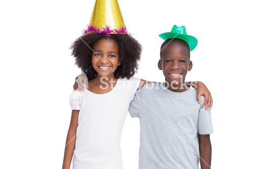 Brother and sister wearing party hats