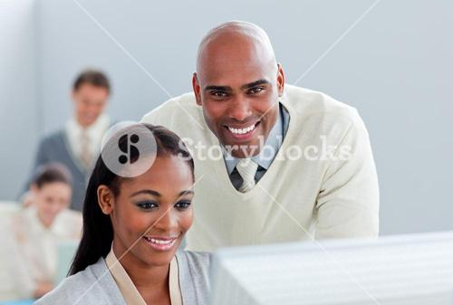 Portrait of two attractive businesspeople working at a computer