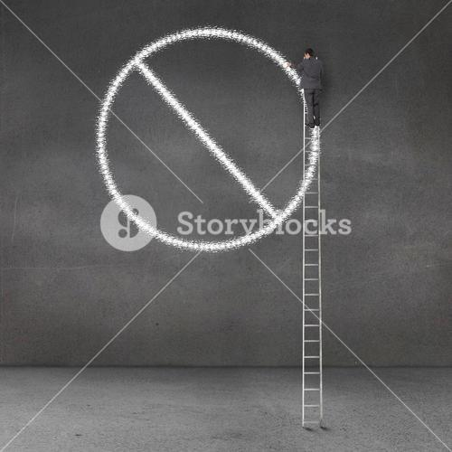 Businessman standing on a giant ladder and drawing forbidden sign