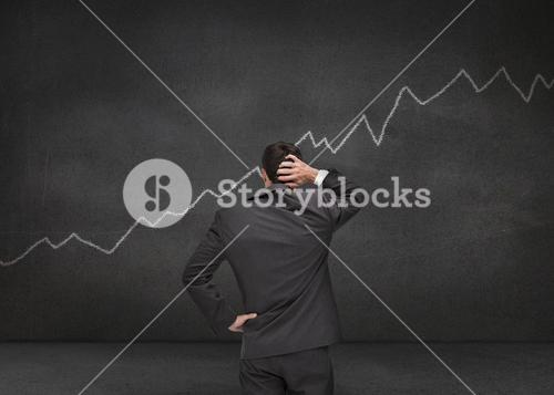 Hesitating businessman looking at white chart