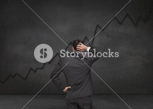 Hesitating businessman looking at black chart