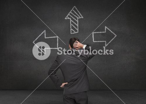 Thoughtful businessman looking at three arrows