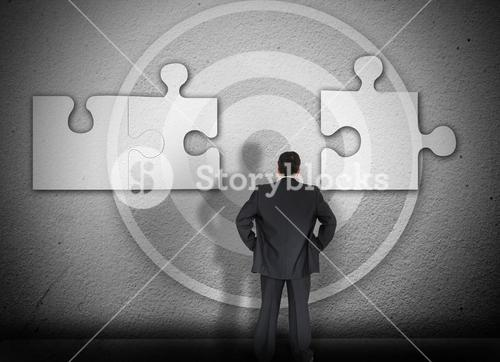 Businessman solving jigsaw puzzle