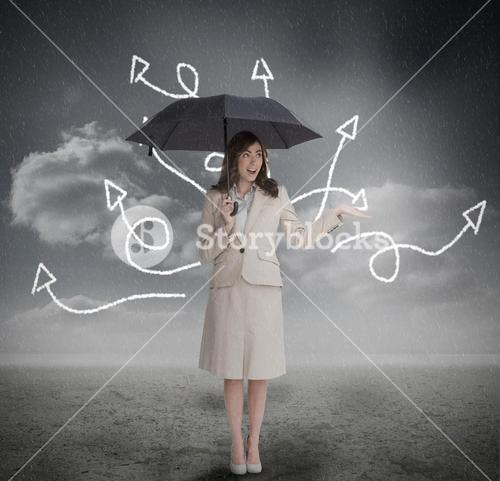 Businesswoman with jumbled arrows holding umbrella