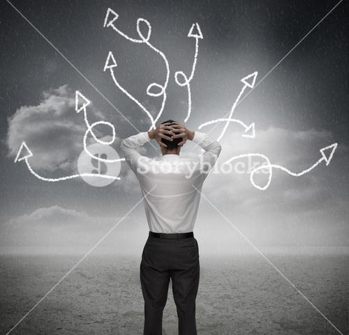 Anxious businessman looking at jumbled arrows