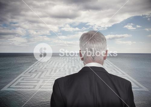 Businessman looking at landscape and maze