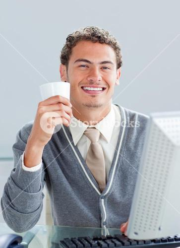 Young businessman drinking a coffe at his desk