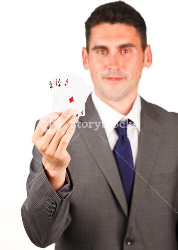 Businessman showing four aces poker cards