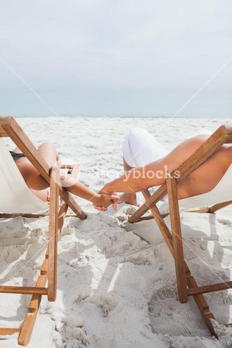 Cute couple lying on deck chairs
