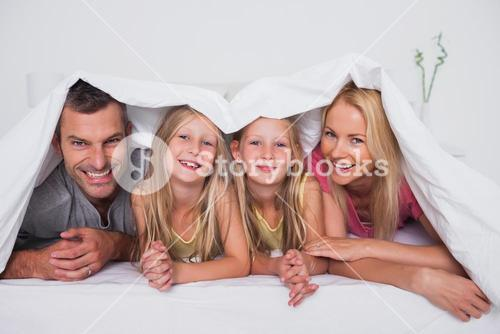 Family playing under the quilt
