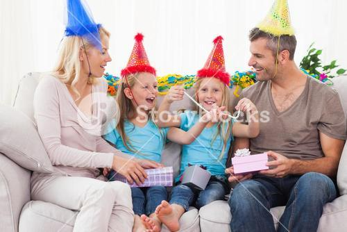Family wearing party hat and celebrating twins birthday
