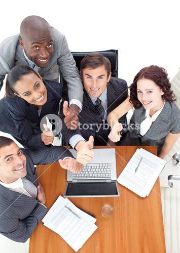 High view of business team with thumbs up working together with a laptop