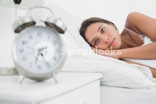 Woman waking up early in bed