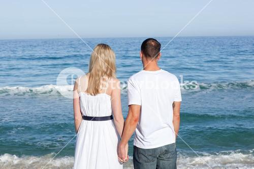 Enamored couple holding hands at the shore line