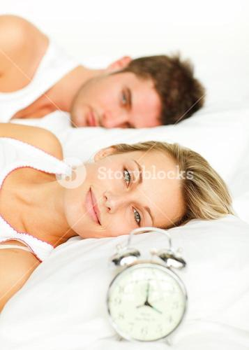 Smiling couple lying on their bed