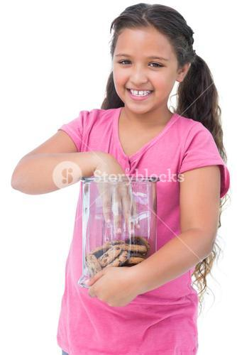 Little girl taking a cookie from jar