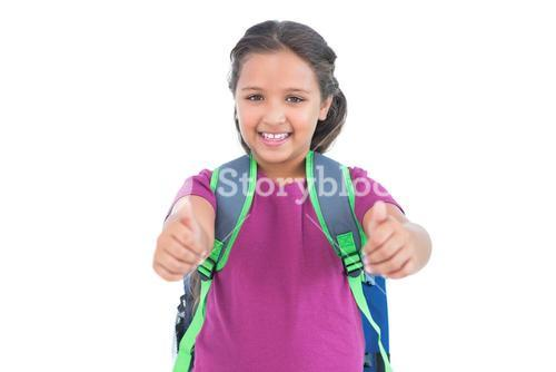 Smiling little girl with book bag does thumbs up at camera
