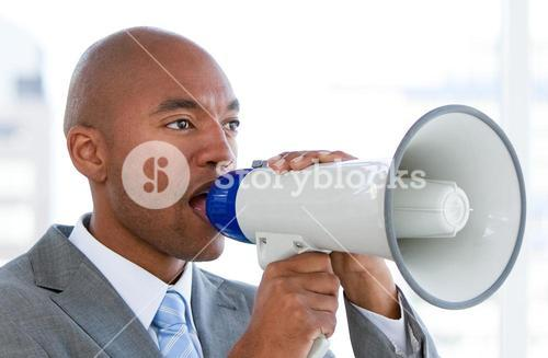 Competitive businessman yelling through a megaphone