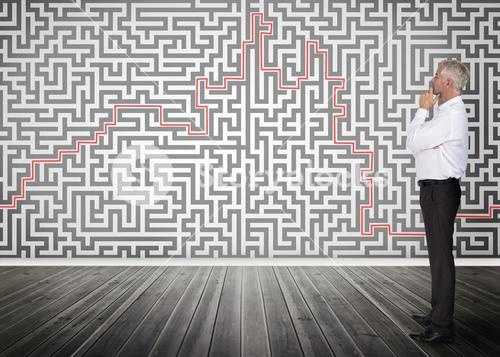 Thoughtful businessman looking at a maze on wall