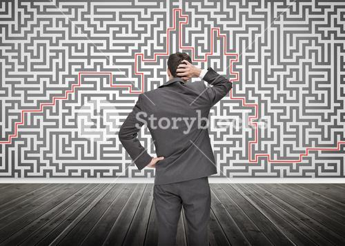 Puzzled businessman looking at a maze