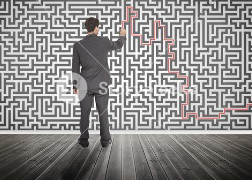 Businessman tracing a red line on a maze
