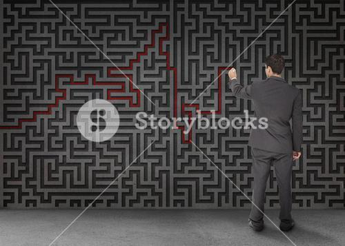 Rear view of a businessman drawing a red line through black maze