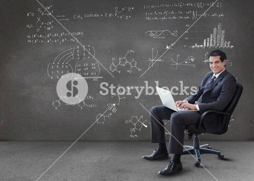 Businessman typing on his laptop with maths equations on wall