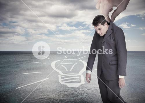 Giant hand dropping off a businessman on a surface