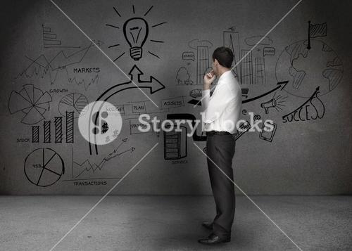 Businessman looking at a wall with drawings