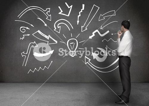 Businessman looking at a wall with drawings of a light bulb