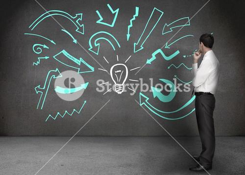 Businessman looking at a wall with drawings of arrows