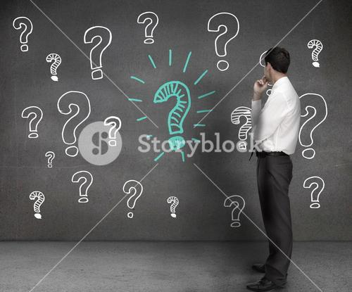 Businessman looking at drawings of question marks