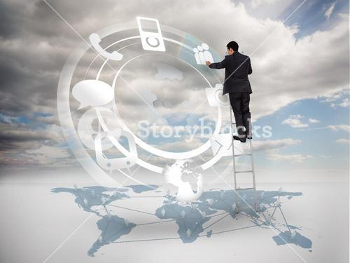 Businessman on a ladder selecting an icon on a hologram