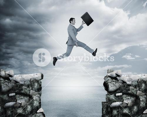 Businessman jumping a gap between cliffs
