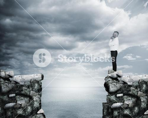Businessman thinking at the edge of a cliff