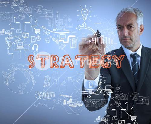 Elegant businessman holding a marker and writing strategy