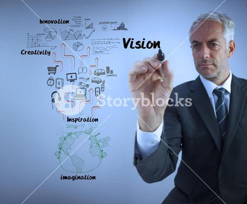 Elegant businessman writing the word vision with a marker