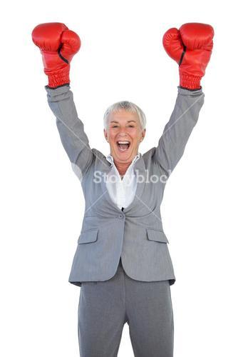 Happy businesswoman wearing boxing gloves and raising her arms