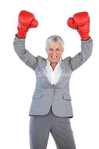 Businesswoman wearing boxing gloves and raising her arms