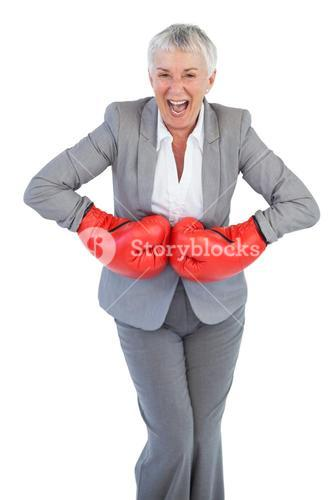 Happy businesswoman wearing boxing gloves