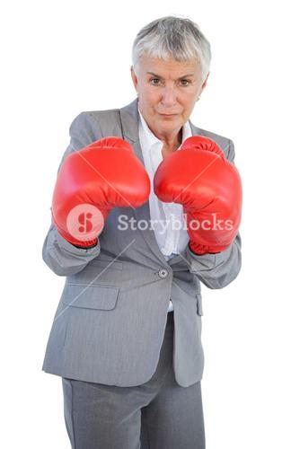 Serious businesswoman standing with her boxing gloves