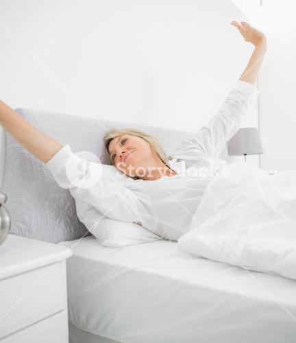 Blonde woman waking up and stetching