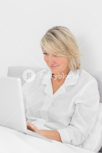 Content woman sitting in bed with laptop