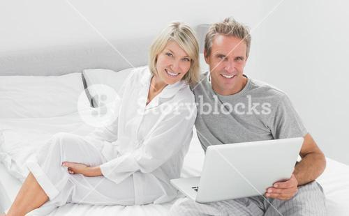 Couple with laptop smiling at camera